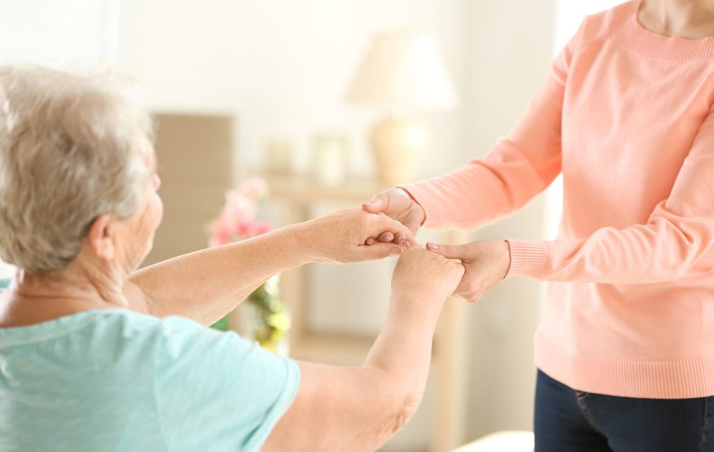 Old and young women holding hands on blurred background