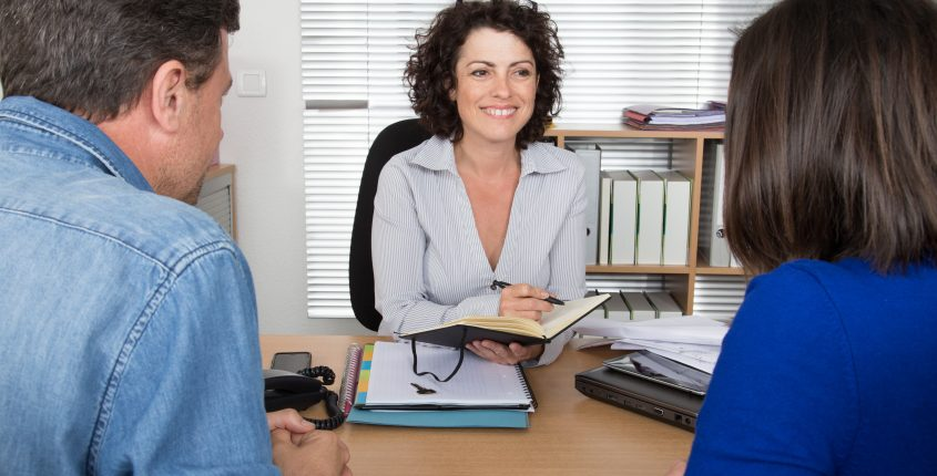 Couple sitting in meeting making investment at desk