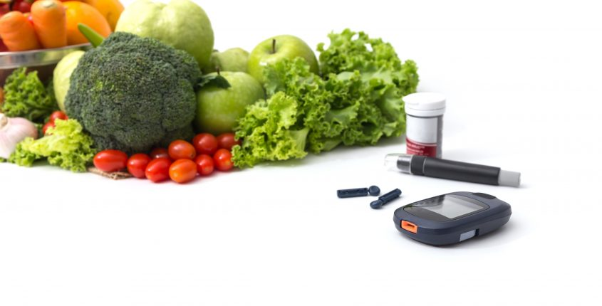 Glucose meter with  fresh  raw vegetables and fruits , desk of healthy organic vegetables, concept for healthy eating and diabetes.